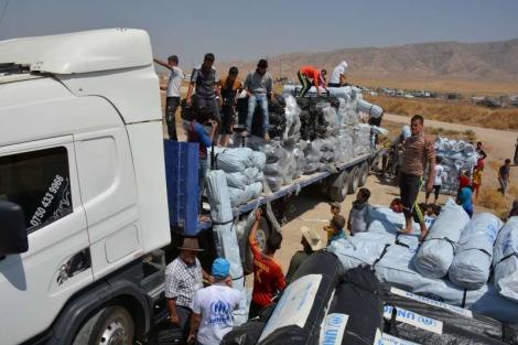 Funcionários da ONU descarregam caminhões com centenas de tendas para as famílias deslocadas no Iraque. Foto: ACNUR/E. Colt