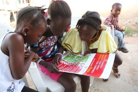 Meninas na Libéria leem um pôster com informações sobre o ebola. Foto: UNICEF/Jallanzo